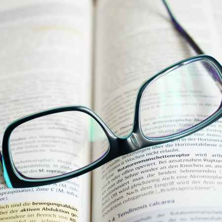 reading a dictionary with glasses for words